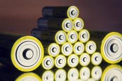 Baterías amarillas del doble A que reflejan en el espejo, concepto del almacenamiento de la electricidad Fotografía de archivo
