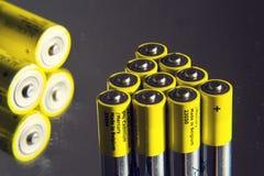 Baterías amarillas del doble A que reflejan en el espejo, concepto del almacenamiento de la electricidad Foto de archivo