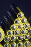 Baterías amarillas del doble A que reflejan en el espejo, concepto del almacenamiento de la electricidad Imagenes de archivo