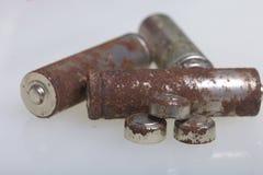 Baterías de corrosión de diversos formas y tamaños Las mentiras sueltan en un fondo blanco Protección del medio ambiente, recicla Imágenes de archivo libres de regalías