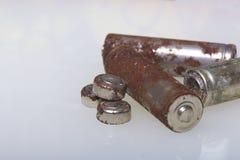 Baterías de corrosión de diversos formas y tamaños Las mentiras sueltan en un fondo blanco Protección del medio ambiente, recicla Fotografía de archivo libre de regalías