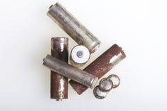 Baterías de corrosión de diversos formas y tamaños Las mentiras sueltan en un fondo blanco Protección del medio ambiente, recicla Imagen de archivo