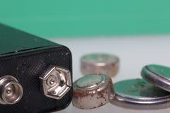 Baterías de corrosión de diversos formas y tamaños Mienten dispersado en una superficie blanca, en un fondo verde RRPP ambientale Imágenes de archivo libres de regalías