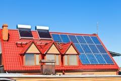 Baterías solares y calentadores en el tejado casero Fotos de archivo libres de regalías