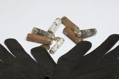 Baterías usadas de la finger-herida cubiertas con la corrosión Guantes de trabajo siguientes reciclaje imagen de archivo libre de regalías