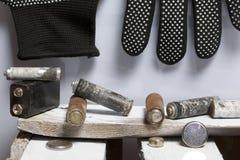 Baterías usadas de la finger-herida cubiertas con la corrosión Mienten en una caja de madera Guantes de trabajo siguientes recicl imagen de archivo libre de regalías