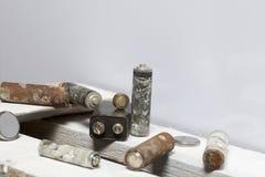 Baterías usadas de la finger-herida cubiertas con la corrosión Mienten en una caja de madera reciclaje imagenes de archivo