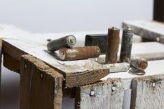 Baterías usadas de la finger-herida cubiertas con la corrosión Mienten en una caja de madera reciclaje imagen de archivo libre de regalías