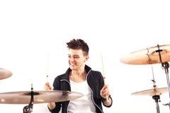 Batería joven expresivo que juega en los tambores con el palillo del tambor Fotos de archivo libres de regalías