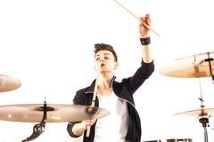 Batería joven expresivo que juega en los tambores con el palillo del tambor Foto de archivo