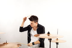 Batería joven expresivo que juega en los tambores con el palillo del tambor Foto de archivo libre de regalías