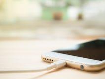 Bateria de carregamento de Smartphone na tabela de madeira Fotografia de Stock
