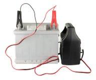 Bateria de carro com os dois cabos da ligação em ponte grampeados aos terminais isolados no branco Foto de Stock