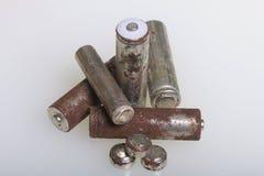 Baterias de corrosão de vários formas e tamanhos As mentiras afrouxam em um fundo branco Proteção ambiental, reciclagem do usado fotografia de stock