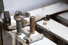 Baterias usadas da dedo-ferida cobertas com a corrosão Encontram-se em uma caixa de madeira Luvas de trabalho seguintes recycling fotografia de stock royalty free