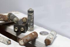 Baterias usadas da dedo-ferida cobertas com a corrosão Encontram-se em uma caixa de madeira recycling fotografia de stock royalty free