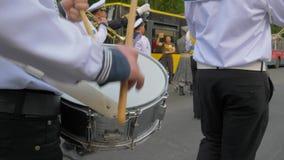 Baterista na banda, marinheiro novo com as varas em jogos do close-up das mãos no cilindro grande durante a parada na rua video estoque