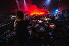 Baterista na fase silhueta da faixa da música na ação na fase da música o grupo de rock da música popular executa na fase fotografia de stock