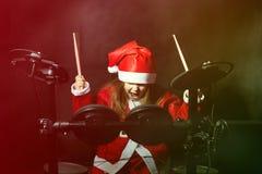 Baterista pequeno disfarçado como Santa Claus que joga o jogo eletrônico do cilindro Fotos de Stock