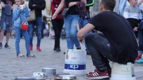 Baterista que joga a música em uma cubeta e em pratos na rua na frente da audiência dos povos filme