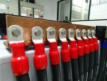 Bateryjna banka groszaka busbar pozytywnego słupa czerwień w staci, ciasto naleśnikowe Zdjęcia Stock