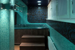 Stairs to jacuzzi in spa salon. Luxurious bathroom interior in turquoise hues with wooden details royalty free stock photo