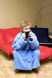 After a bath. Teen  in a cosy light-blue bathrobe Royalty Free Stock Photo