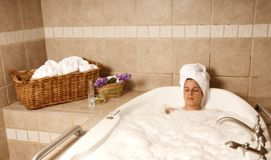 In the bath. Cute girl in a spa bath relaxing Stock Photo