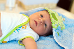 Before bath. Five weeks thoughtful baby lying on bathing towel. Towel covers baby's head royalty free stock images