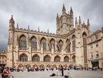 Bath Abbey at Bath Somerset South West England UK. BATH, UK - JUN 11, 2013: Street musician buskin at the Abbey Church of Saint Peter and Saint Paul, commonly Royalty Free Stock Photo