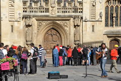 Bath Abbey. BATH, UK - May 1, 2014: Tourists and locals enjoy a sunny day in the courtyard of the historic Bath Abbey and Roman Baths. The Somerset city receives Royalty Free Stock Image