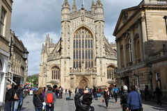 Bath Abbey. BATH, UK - May 1, 2014: Tourists and locals enjoy a sunny day in the courtyard of the historic Bath Abbey and Roman Baths. The Somerset city receives Stock Photo