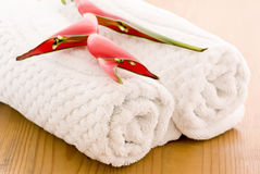 Bath accessories. Bath towels with red heliconia on the wooden floor Stock Image