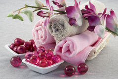 Bath accessories. Bath oil pearls and towels Royalty Free Stock Photo
