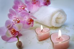 Bath accessories. Towel and perfumeв candles with tender orchids Stock Photos