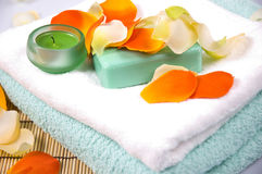 Bath accessories. Soap, towel, candle and flower petals - bath accessories Royalty Free Stock Image