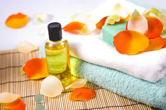 Bath accessories. Soap, towel, flower petals and oil - bath accessories royalty free stock photo