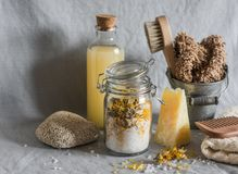 Bath accessories - homemade sea salt with calendula, natural shampoo, brush, washcloth, pumice, homemade oat soap. Health, beauty. Concept. Flat lay stock photography