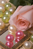 Bath accessories and rose. Various color oil pearls and pink rose Stock Images