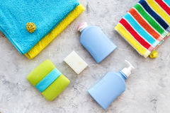 Bath accessories. Towels, soap, shampoo, washclothes on grey background top view copyspace Royalty Free Stock Photos