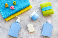 Bath accessories. Towels, soap, shampoo, washclothes on grey background top view copyspace Stock Photography