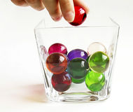 Bath balls in a container. A hand putting a ball into the glass container Stock Photo