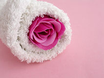Bath beauty. A rolled towel with a rose on pink background Stock Photos