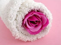 Bath beauty. A rolled white towel with a pink soap rose on pink background Royalty Free Stock Photos