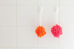 Bath body scrubbers. Two colorful bath body scrubbers on tiled shower wall Stock Photos