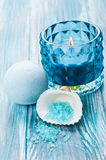 Bath bomb closeup with blue lit candle Royalty Free Stock Images