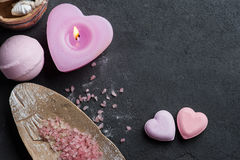 Bath bomb closeup with pink lit candle. SPA still life, pink heart shaped bath bombs, salt with lit candle on concrete background. Flat lay, view from above Stock Photos