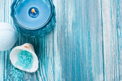 Bath bombs closeup with blue lit candle. SPA still life, closeup of blue lit candle, salt and bath bombs on wooden background. Space for text Stock Images