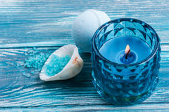Bath bombs closeup with blue lit candle. SPA still life, closeup of blue lit candle, salt and bath bombs on wooden background. Space for text Stock Photo
