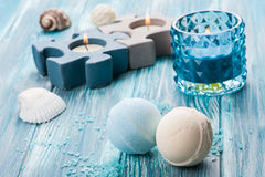 Bath bombs closeup with blue lit candle. SPA still life, closeup of blue lit candle and bath bombs on wooden background Stock Images